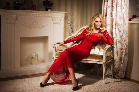 Beautiful blonde in a red dress sitting on the couch  in the vintage interior   photo