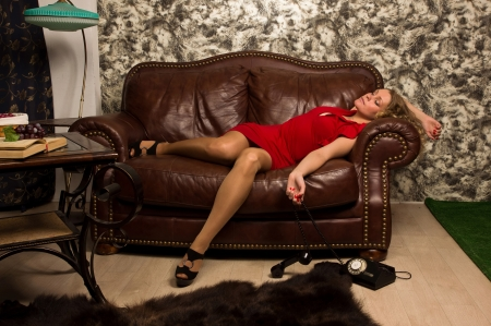 Crime scene simulation: lifeless blonde in the red dress lying on the sofa