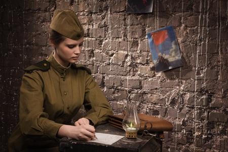Soviet female soldier in uniform of WW II writes a letter photo