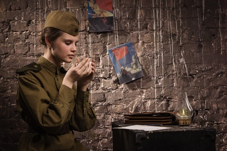 Soviet female soldier in uniform of World War II in the dugout photo