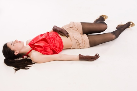 Lifeless brunette in red lying on the floor photo