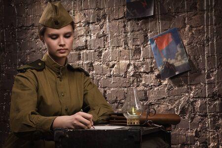 Soviet female soldier in uniform of World War II writes a letter photo