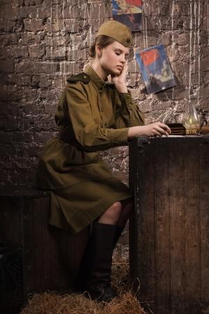 Soviet female soldier in uniform of World War II reads the letter photo
