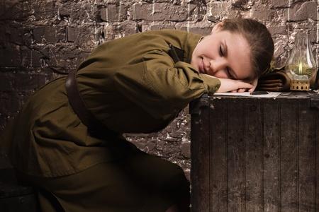 Soviet female soldier in uniform of World War II sleeping in the dugout photo