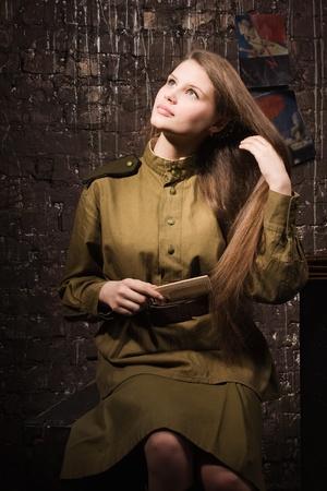 Soviet female soldier in uniform of World War II combs her hair photo