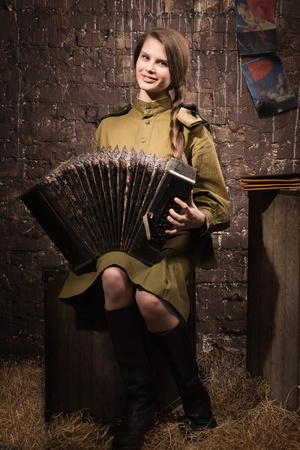 Soviet female soldier in uniform of World War II with an old accordion photo