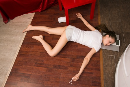 Crime scene simulation: overdosed victim lying on the floor photo
