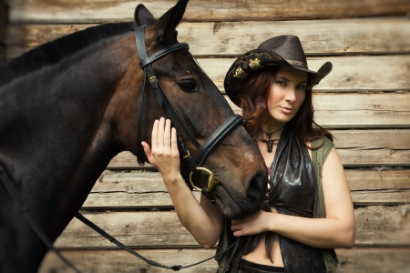 Young cowgirl with brown horse on the ranch photo