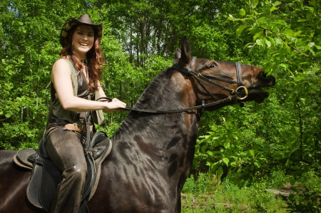 Young cowgirl on brown horse photo