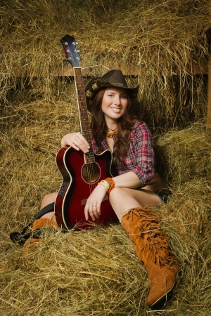 Pretty country girl with guitar on the ranch photo