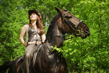 Young cowgirl on brown horse Stock Photo