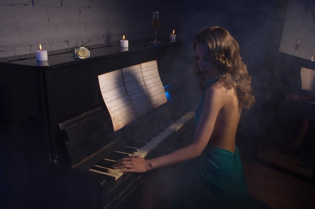 evening dress: Pretty woman in evening dress playing piano