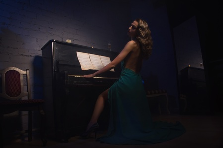 Pretty woman in evening dress playing piano photo