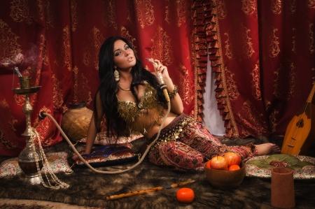 Mooie Arabische vrouw met waterpijp in een harem Stockfoto