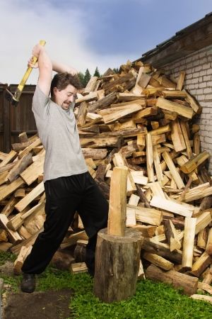 Man with axe chops wood photo