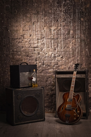 loud music: Electric guitar and old amplifier on a grunge wall background