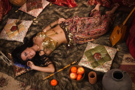 Beautiful belly dancer lying down in the arabic harem interior photo