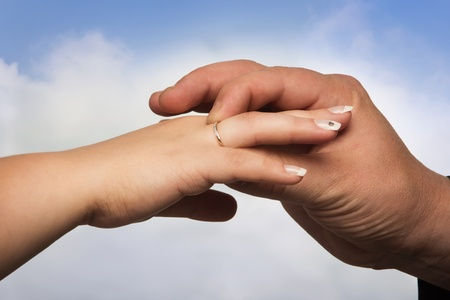 Hand of a man putting a ring on the hand of a woman photo