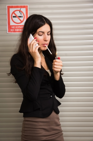 Business woman smokes against signs prohibiting smoking photo