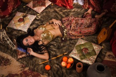 Belle danseuse du ventre couch� dans le harem arabe int�rieur photo