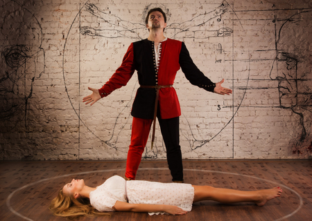 levitating: Magic moment - man in medieval suit performing magically levitating his girl assistant