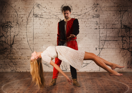 levitation: Magic moment - man in medieval suit performing magically levitating his girl assistant