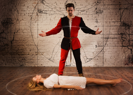 levitating: Magic moment - man in medieval suit performing magically levitating his girl assistant    Stock Photo