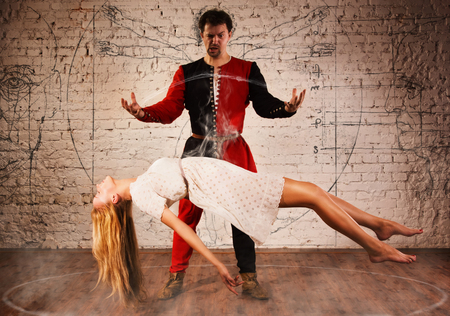 Magic moment - man in medieval suit performing magically levitating his girl assistant photo