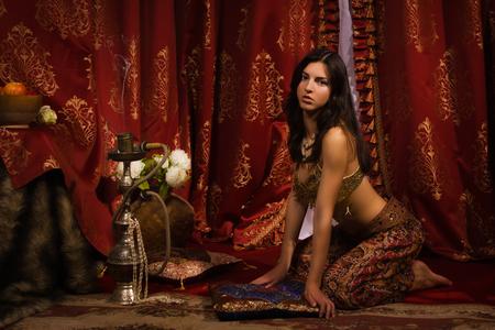 Beautiful belly dancer in the arabic harem interior photo
