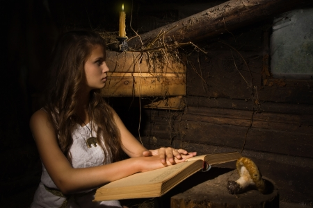 dark interior: Young girl in the traditional suit sitting with old book in a dark interior Stock Photo