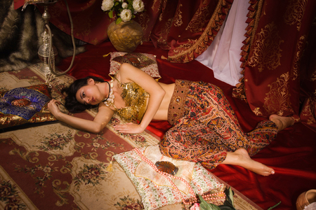 Crime scene imitation: lifeless woman in a traditional oriental costume lying on a floor photo