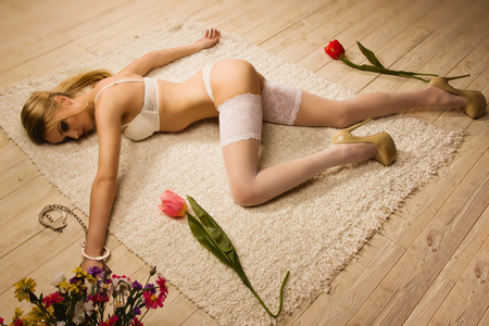 Beautiful blonde woman in handcuffs lying on a floor photo
