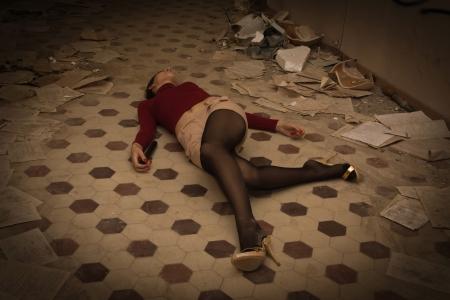 Brunette sans vie en rouge gisant sur le sol