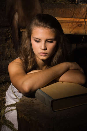 Young girl in the traditional suit sitting with old book in a dark interior photo