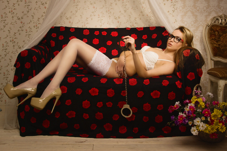 Beautiful blonde woman in a luxurious lingerie with handcuffs photo