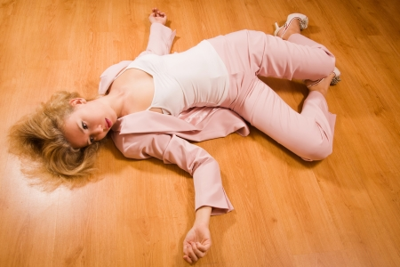 Crime scene simulation: unconscious business woman lying on the floor photo