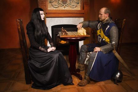 Medieval knight plays chess with death in a castle photo