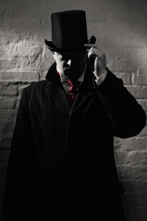 arroganza: L'uomo nel cappotto nero, cappello a cilindro e in una cravatta rossa su uno sfondo di muro