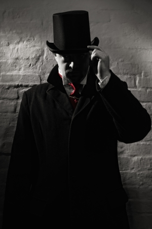 evildoer: Man in the black coat, top hat and in a red tie on a wall background