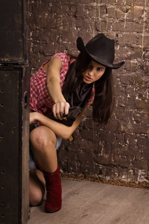 Girl cowboy shoots from a revolver photo