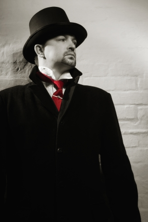 malefactor: Man in the black coat, top hat and in a red tie on a wall background