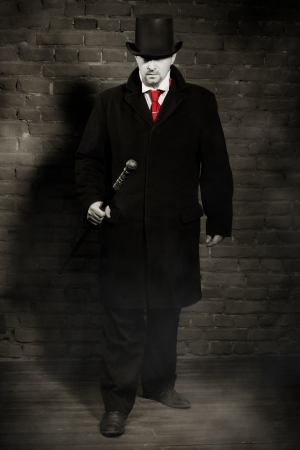 malefactor: Man in the black coat, top hat and in a red tie on a wall background  Stock Photo