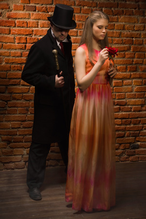 evildoer: Vampire and his victim. Man in the black coat, top hat and in a red tie and beautiful girl with rose