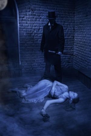 Vampire et sa victime. Homme au manteau noir, chapeau haut de forme et d'une cravate rouge et belle fille à la rose Banque d'images - 23981226