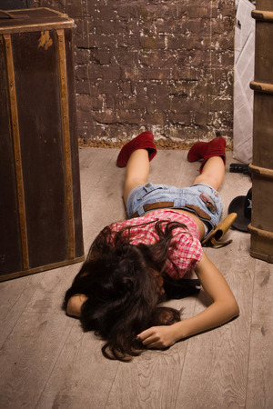 Crime scene in a western style. Lifeless sheriff woman lying on the floor   photo