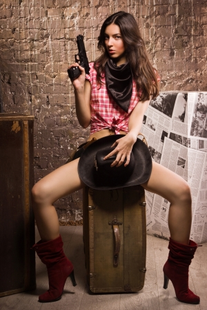 gunfighter: Country girl with gun sitting on a vintage suitcase