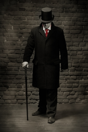 evildoer: Man in the black coat, top hat and in a red tie on a wall  Stock Photo