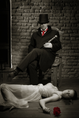 evildoer: Man in the black coat, top hat and in a red tie and beautiful girl with rose Stock Photo