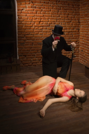 malefactor: Vampire and his victim. Man in the black coat, top hat and in a red tie and beautiful girl with rose
