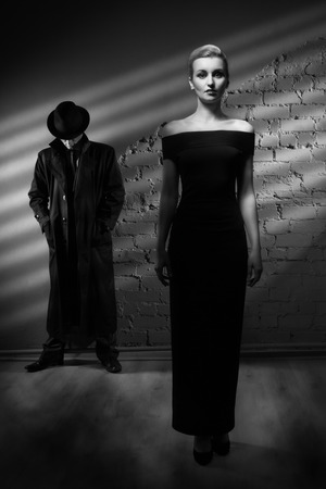 organized crime: Film noir. Woman in a long black dress and a man in a raincoat and hat